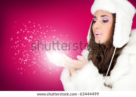 beautiful winter woman blowing snowflakes from her hands - stock photo