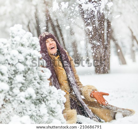 Beautiful winter woman have fun in winter park throwing snowflakes. motion - stock photo