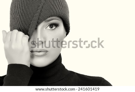 Beautiful winter woman in wool cap covering one eye while looking at camera. Monochrome portrait with copy space for text on the right - stock photo