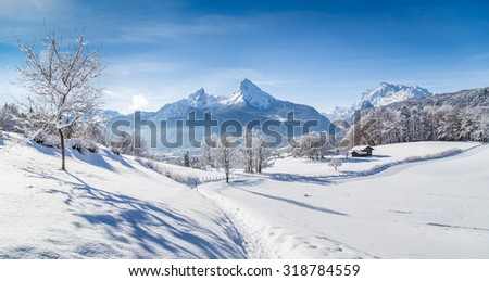 Beautiful winter wonderland scenery with trees and mountain tops in the Alps on a sunny day with blue sky and clouds - stock photo