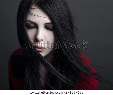 Beautiful witch and Halloween theme: portrait of a girl vampire with black hair - stock photo