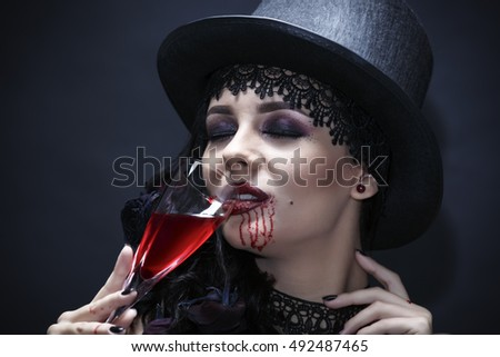 Beautiful witch - drinking red wine - blood