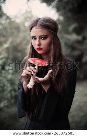 beautiful witch holding a mushroom - stock photo