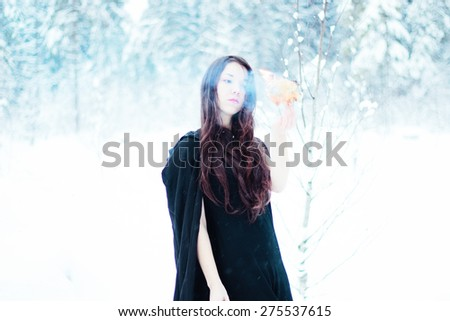 Beautiful witch in black cloak holding fire - stock photo