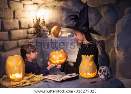 Beautiful witch in black clothing is giving a spooky pumpkin to her child. She is sitting in her cave and looking at the girl with joy. They are celebrating Halloween and smiling - stock photo
