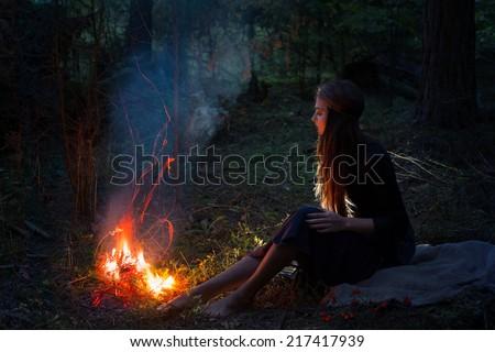 beautiful witch looking at the fire in the forest - stock photo