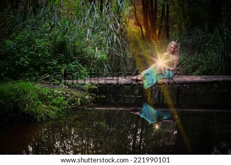 beautiful witch sitting on wooden bridge over the river and practice witchcraft - stock photo