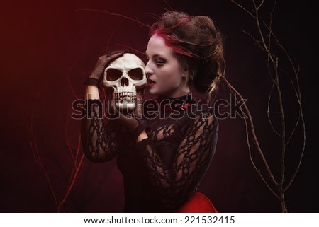 Beautiful witch with a bone in mystery forest. Halloween make-up and costume. - stock photo