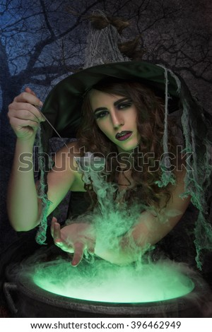 Beautiful witch with magic potion - stock photo