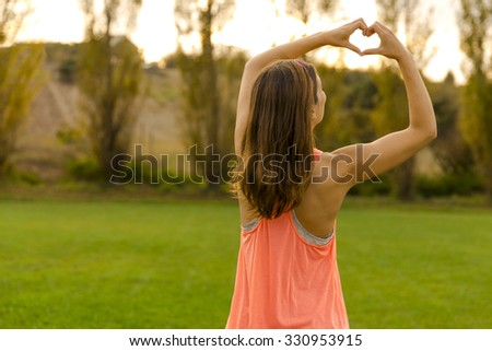 Beautiful woman after the exercise making a hearth shape - stock photo