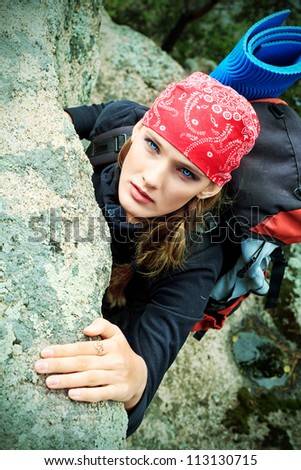 Beautiful woman alpinist is climbing on a mountain. - stock photo