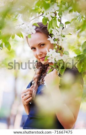 Beautiful woman among a spring blossom - stock photo
