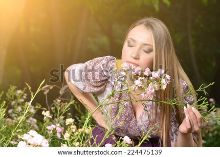 Beautiful woman among blooming trees, Spring , Summer beauty. Young Blonde woman posing on a rose flowers . Horizontal, Outdoor shot. Colorful photography - stock photo