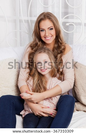Beautiful woman and child at home - stock photo