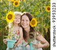 Beautiful woman and child with sunflower in spring field - stock photo