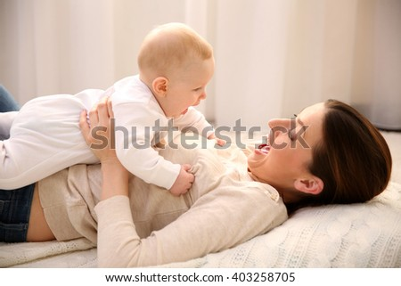 Beautiful woman and cute baby lying on the floor - stock photo