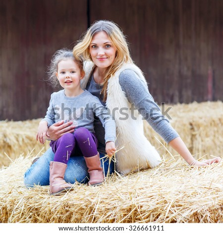 Beautiful woman and cute little girl having fun with hay on a farm. Family of two enjoying autumn season and laughing. Happy childhood, family, lifestyle concept. - stock photo