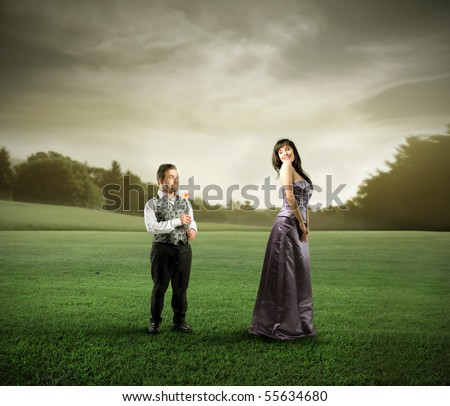 Beautiful woman and dwarf standing on a green meadow - stock photo