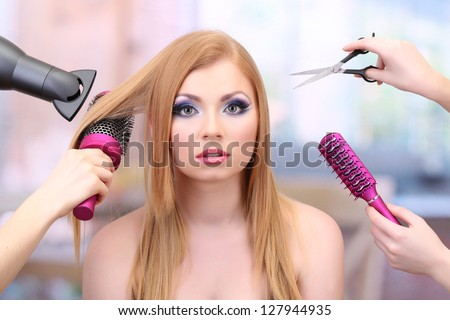 Beautiful woman and hands with brushes, scissors and hairdryer in beauty salon - stock photo