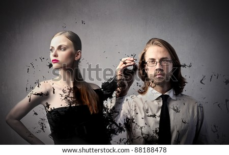 Beautiful woman and handsome fashion designer drawing her dress - stock photo