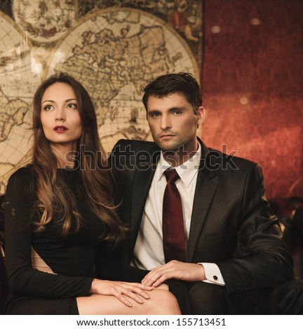 Beautiful woman and handsome young man sitting on a sofa in luxury interior  - stock photo