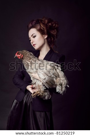 Beautiful woman and hen. Studio shot - stock photo