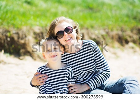 Beautiful woman and her son resting on the beach - stock photo