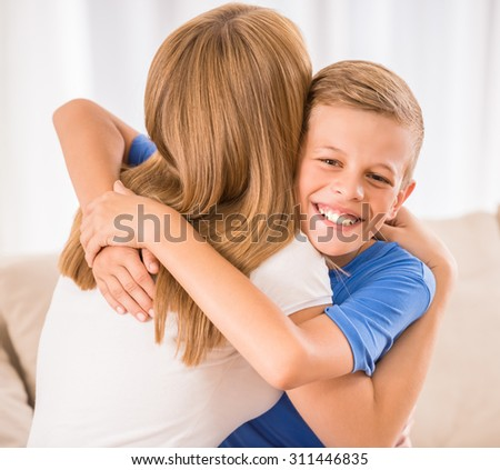 Beautiful woman and her teenage son are hugging at home. - stock photo