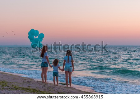 Beautiful woman and her two daughters walking along the beach at sunrise - stock photo