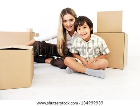 Beautiful woman and little child openig cardboard box - stock photo