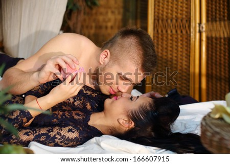 Beautiful woman and man lie on bamboo bed and touch each other noses in bedroom. - stock photo