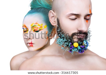 Beautiful woman and man with colorful makeup on white background, flowers on man beard - stock photo