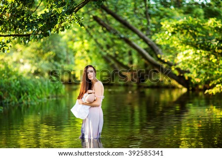 beautiful woman and mother with long  brunette hair in long dress feeding milk the infant baby outdoors in the water of the river
