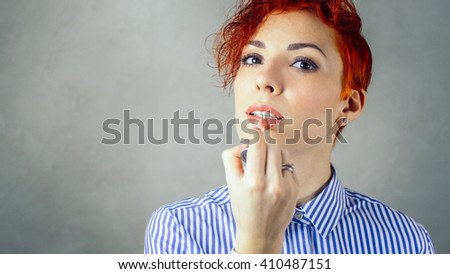 Beautiful woman applies glossy lipstick on lips. Perfect face makeup. Young woman with lip brush. Girl applying professional makeup. Beauty fashion make-up portrait. Stylish woman with red short hair. - stock photo