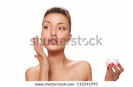 beautiful woman applying a skincare cream on her face - stock photo