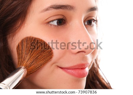 Beautiful woman applying blush on her face - stock photo
