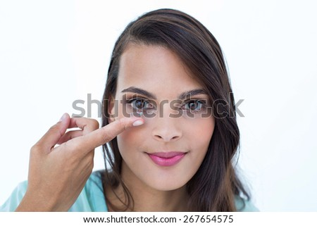 Beautiful woman applying contact lens on white background