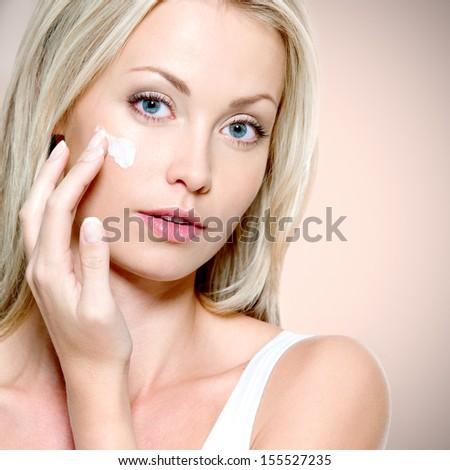 Beautiful woman applying cosmetic cream on face - stock photo