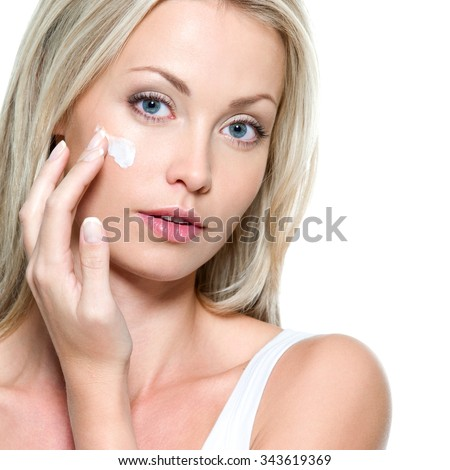 Beautiful woman applying cosmetic cream on face - isolated - stock photo