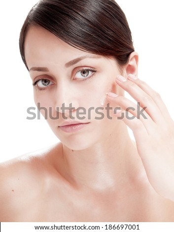 Beautiful woman applying cosmetic cream treatment on her face. Skin care concept.  - stock photo