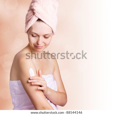 beautiful woman applying cream after bath - stock photo