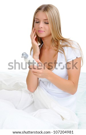 beautiful woman applying cream on her cheek . Isolated on white background - stock photo