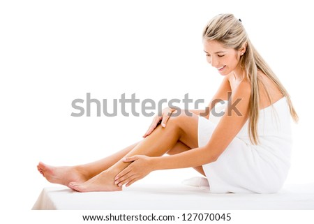 Beautiful woman applying cream on her legs - isolated over white