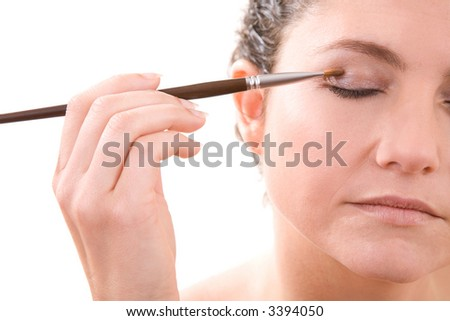 Beautiful woman applying eyeshadow with a soft brush - stock photo