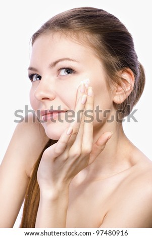 beautiful woman applying face cream isolated on white