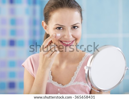 Beautiful woman applying facial cream.