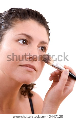 Beautiful woman applying foundation with a big brush on white background - stock photo