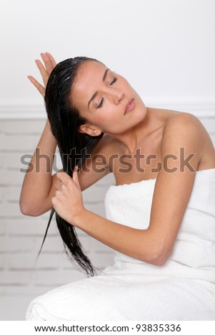 Beautiful woman applying hair conditioner - stock photo