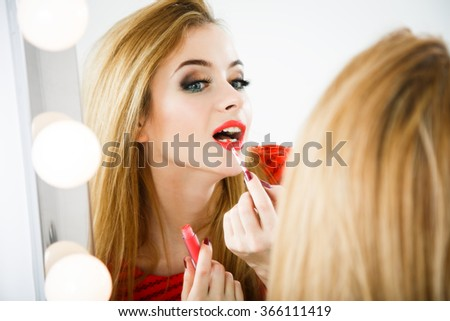Beautiful Woman Applying Lipstick at the Mirror