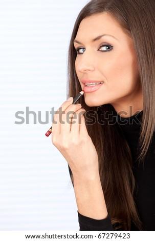 beautiful woman applying lipstick using lip concealer brush - stock photo